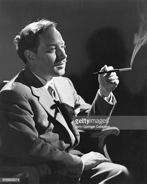 Photo of American Playwright Tennessee Williams , seated and smoking a cigarette with a cigarette holder. Undated photo.