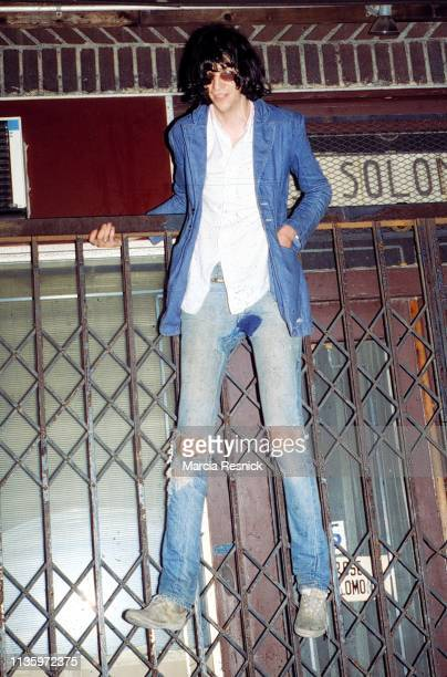 Photo of American Punk musician Joey Ramone of the Ramones perched on a gate in front of a closed business on the Bowery New York New York 1978