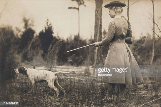 Photo of American sharpshooter Annie Oakley and her dog Dave as they hunt quail circa 1908