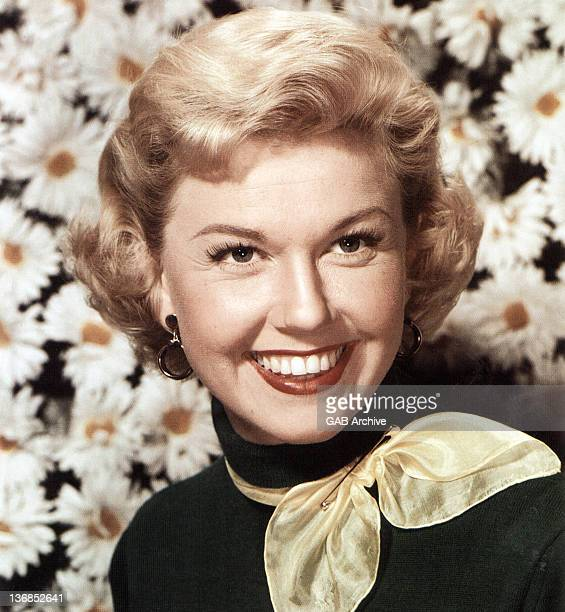 Photo of American singer and actress Doris Day posed wearing a yellow neckerchief in front of a backdrop of large daisies circa 1950