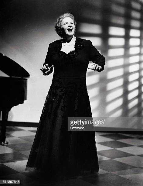Photo of American singer and actress Kate Smith shown midsong Star is wearing a black dress and a piano is at her right