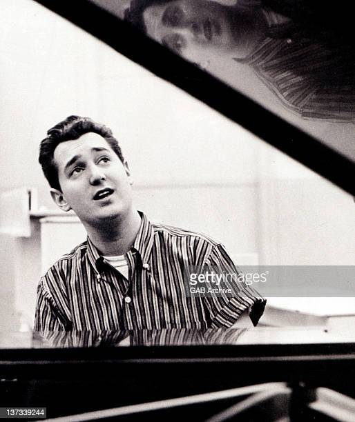 Photo of American singer and songwriter Neil Sedaka posed sitting at a piano circa 1960