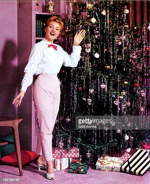 Photo of American singer Patti Page posed in front of a Christmas tree and presents circa 1955