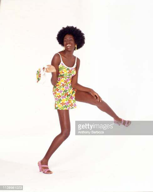 Photo of an unidentified model dressed in a floral print sundress as she poses against a white background New York 1990s