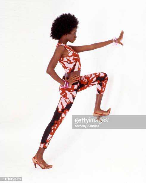 Photo of an unidentified model dressed in a matching top and bottom with a red white and black floral print as she poses against a white background...