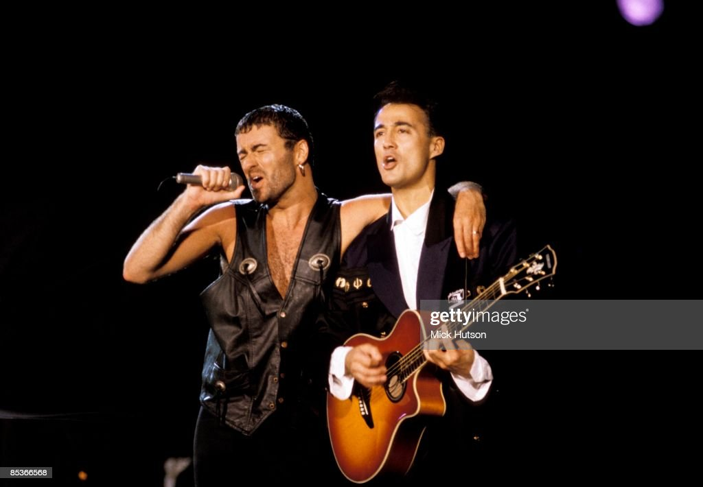 III Photo of Andrew RIDGELEY and George MICHAEL and WHAM!, Andrew Ridgeley (playing Yamaha acoustic guitar) appearing with George Michael at solo performance, performing live onstage