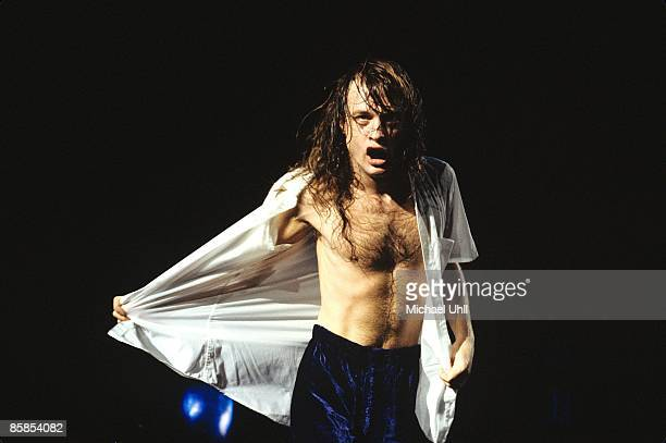 GARDEN Photo of Angus YOUNG and AC/DC Angus Young performing on stage taking shirt off