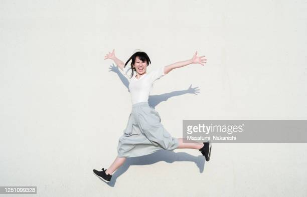 photo of asian woman jumping with smile in front of white wall - jumping stock pictures, royalty-free photos & images