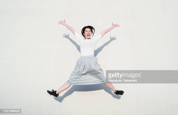 白い壁の前で笑顔でジャンプするアジアの女性の写真 - 喜び ストックフォトと画像