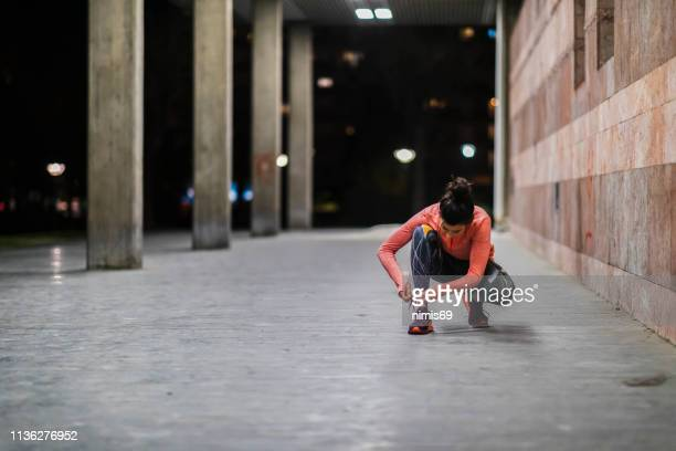 photo of athlete tying shoelaces on sports sneakers - tying shoelace stock pictures, royalty-free photos & images