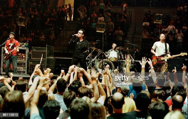 Photo of AUDIENCE and U2; L-R: The Edge, Bono, Larry Mullen Jnr, Adam Clayton performing live onstage on the 1st date of Elevation tour, showing fans...