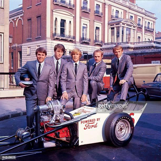 Photo of BEACH BOYS; Carl Wilson, Brian Wilson, Dennis Wilson, Mike Love, Al Jardine, posed group portrait with a hot rod car -
