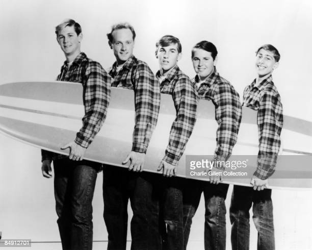 Photo of BEACH BOYS; L-R: Brian Wilson, Mike Love, Dennis Wilson, Carl Wilson, David Marks posed with surfboard