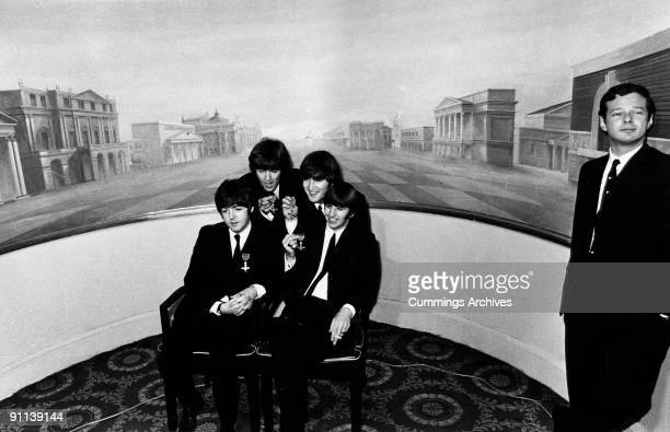 Photo of BEATLES and Brian EPSTEIN; L-R. Paul McCartney, George Harrison, John Lennon, George Harrison, Brian Epstein, receiving MBE's at Buckingham...
