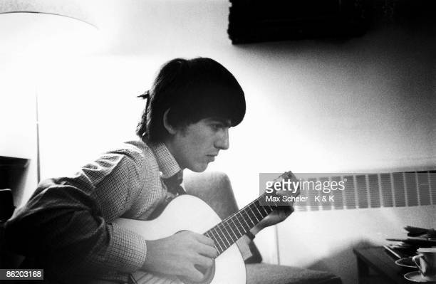 Photo of BEATLES and George HARRISON, of Beatles, posed, playing nylon string acoustic guitar at Twickenham Film Studios, during the filming of 'A...