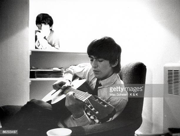TWICKENHAM Photo of BEATLES and George HARRISON of Beatles posed playing nylon string acoustic guitar at Twickenham Film Studios during the filming...