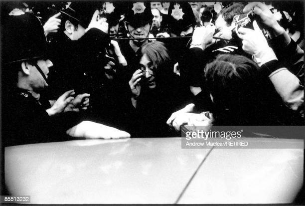 Photo of BEATLES and John LENNON John Lennon surrounded by Police as they try to get in to a car to leave Marylebone Magistrates Court after...