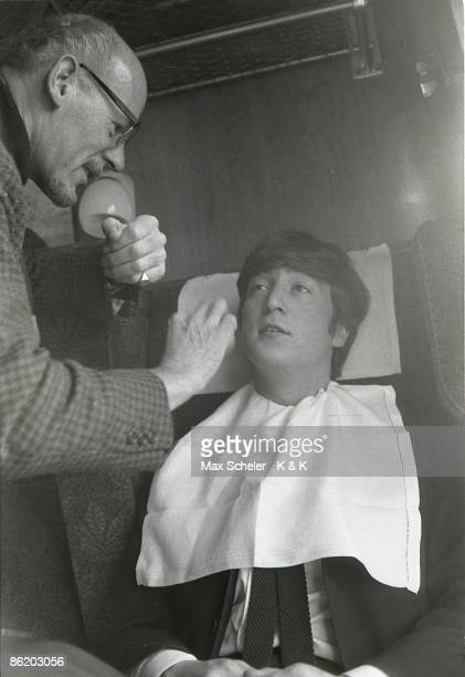 Photo of BEATLES and John LENNON of The Beatles having makeup applied on train during the filming of 'A Hard Day's Night'