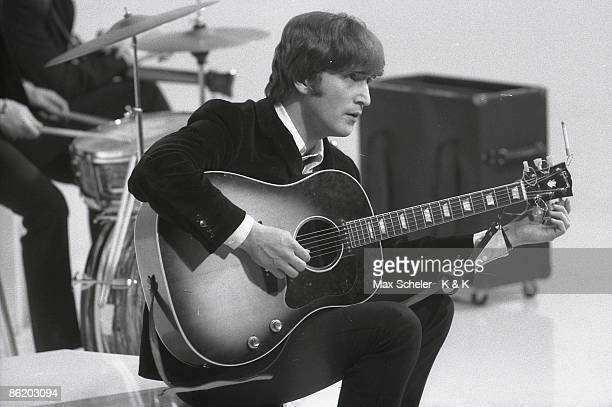 Photo of BEATLES and John LENNON of the Beatles tuning guitar during the filming of A Hard Day's Night at the Scala Theatre
