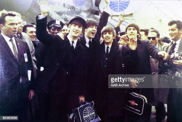 Photo of BEATLES LR John Lennon Paul McCartney Ringo Starr George Harrison group shot waving at crowds arriving at JFK airport for first US tour