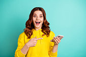 Photo of beautiful cheerful ecstatic attractive curly wavy trendy stylish youngster pointing at telephone held with hands wearing yellow sweater hoodie isolated over vivid teal color background