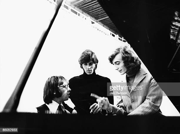 Photo of BEE GEES posed together at a piano Left to right Maurice Gibb Barry Gibb and Robin Gibb