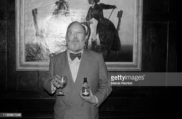 Photo of Belgian-born American museum curator Henry Geldzahler as he holds a glass and a bottle of Perrier water at the Literary Gold Medal Awards...