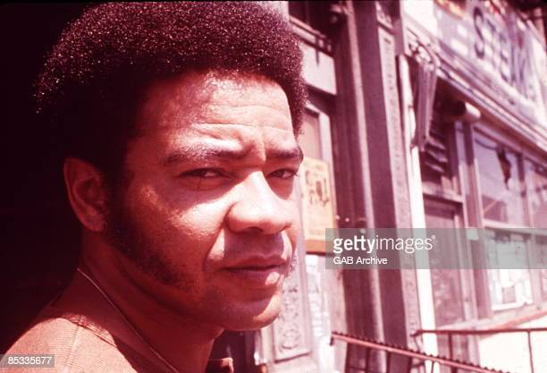 Photo of Bill WITHERS; Posed portrait of Bill Withers in the street
