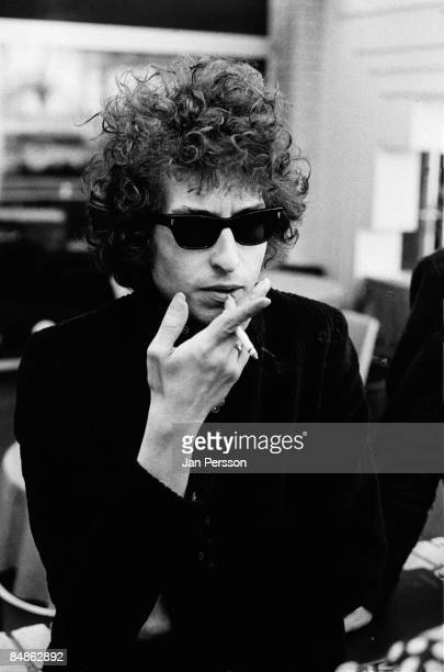 Photo of Bob DYLAN posed at press conference smoking wearing sunglasses