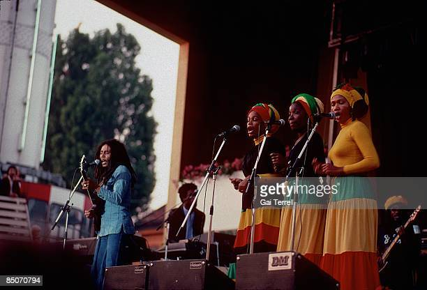 Photo of Bob MARLEY and WAILERS and I THREES Bob Marley performing on stage with the I Threes