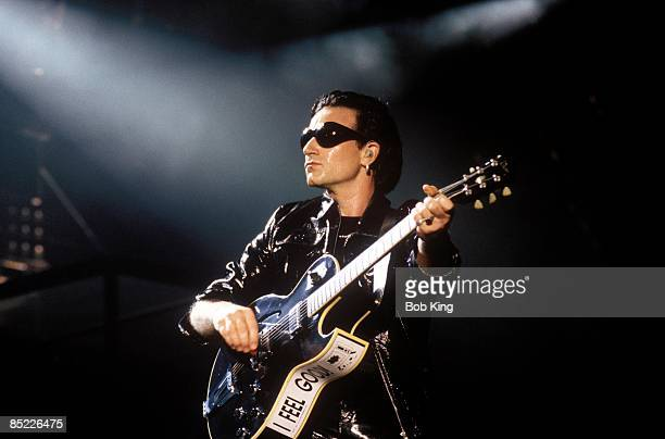 Photo of BONO and U2 Bono performing live onstage at the Aussie Stadium on the Zoo TV tour Zoomerang leg playing guitar wearing sunglasses