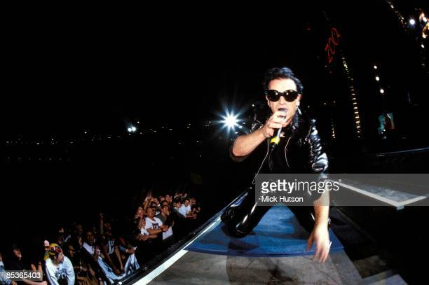 STADIUM Photo of BONO and U2 Bono performing live onstage on Zoo TV Zooropa tour wearing leather suit and sunglasses looking to camera showing front...