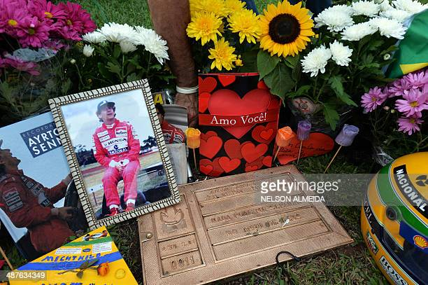 A photo of Brazilian's F1 driver Ayrton Senna is seen among flowers left by fans in his grave in Sao Paulo Brazil on May 1 paying tribute to the 20th...