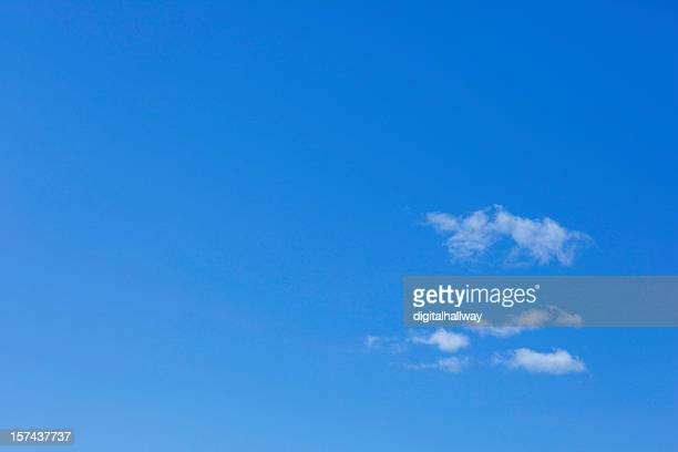 Photo of bright blue sky with small clouds forming on right