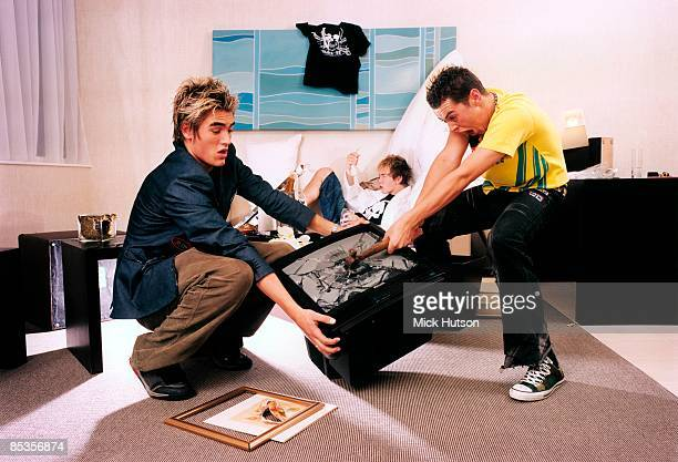 Photo of BUSTED and Charlie SIMPSON and James BOURNE and Matt WILLIS Group portrait LR Charlie Simpson James Bourne and Matt Willis trashing tv in...