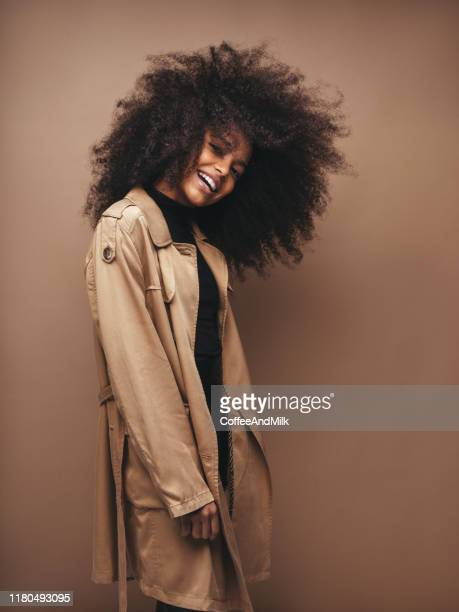 photo of cheerful curly woman with positive emotions - black jacket stock pictures, royalty-free photos & images