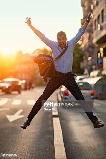 Photo of cheerful man jumping with arms stretched up