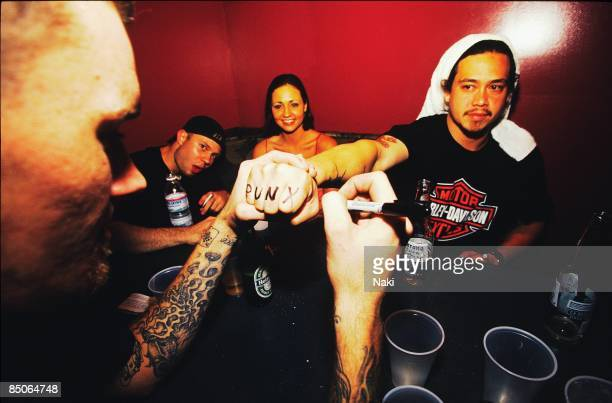 Photo of Chi CHENG and DEFTONES Chi Cheng posed backstage with fans writing PUNX on knuckles