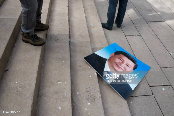 Photo of Chinese President Xi Jinping in pictured on the ground as Uyghur activists protest China's treatment of Uyghurs outside a court appearance...