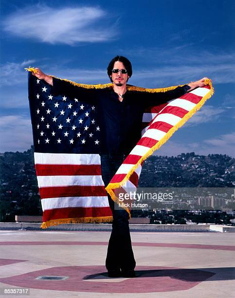 Photo of Chris CORNELL Posed full length portrait of Chris Cornell on rooftop with Stars and Stripes flag 358