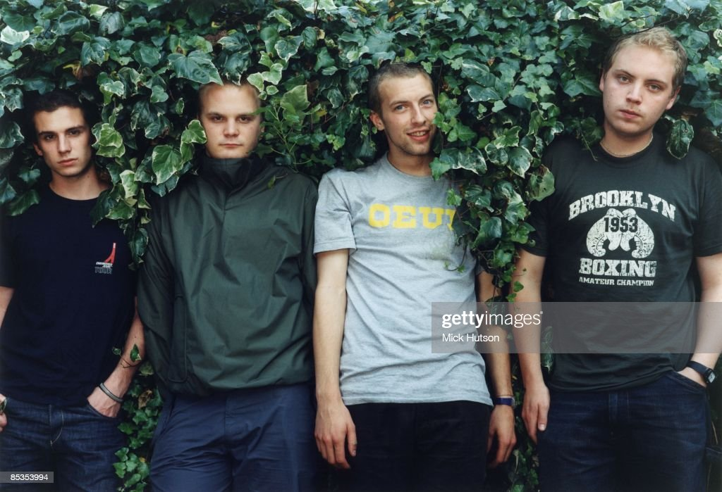 Photo of Chris MARTIN and COLDPLAY and Jonny BUCKLAND and Will CHAMPION and Guy BERRYMAN; Posed group portrait in hedge L-R Guy Berryman, Will Champion, Chris Martin and Jonny Buckland