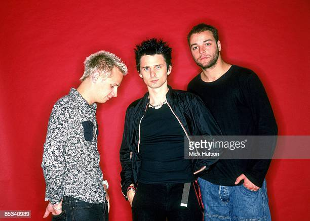 Photo of Chris WOLSTENHOLME and Matt BELLAMY and Dominic HOWARD and MUSE; L-R: Dominic Howard, Matt Bellamy, Chris Wolstenholme - posed, studio