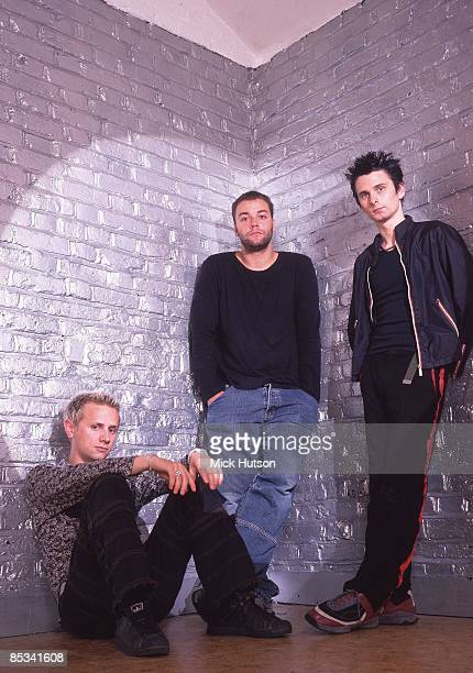 Photo of Chris WOLSTENHOLME and Matt BELLAMY and Dominic HOWARD and MUSE; L-R: Dominic Howard, Chris Wolstenholme, Matt Bellamy - posed, studio