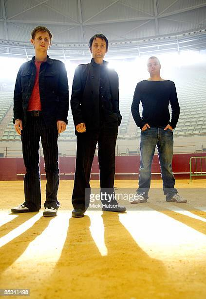 Photo of Chris WOLSTENHOLME and MUSE and Dominic HOWARD and Matt BELLAMY; L-R: Dominic Howard, Matt Bellamy, Chris Wolstenholme - posed, group shot
