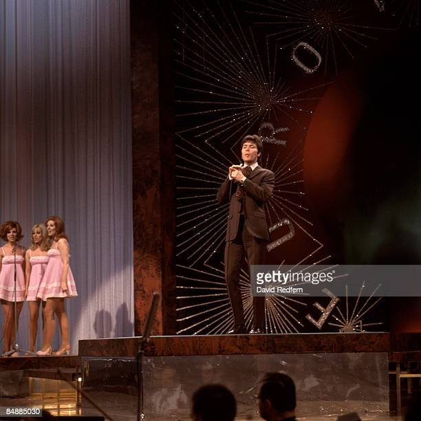 HALL Photo of Cliff RICHARD performing live onstage at the Eurovision Song Contest with Eurovision logo behind