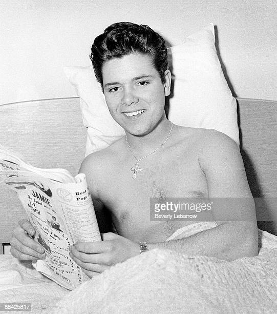 Photo of Cliff RICHARD posed lying in bed reading magazine c1958/1959