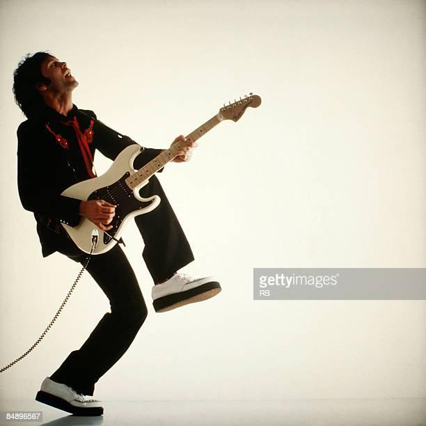 Photo of Cliff RICHARD Posed studio portrait of Cliff Richard full length profile guitar