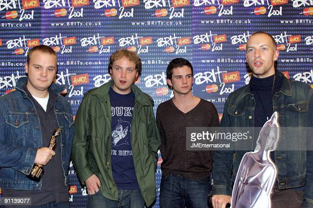 Will Champion Jonny Buckland Guy Berryman Chris Martin posed group shot holding Brit Award
