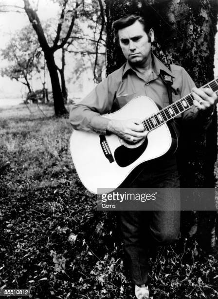 Photo of Country musician George JONES posed playing an acoustic guitar circa 1970