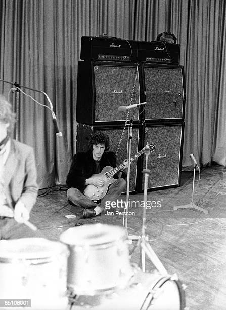 Photo of CREAM and Eric CLAPTON Eric Clapton sitting on stage with Gibson Les Paul guitar in front of stack of Marshall Amplifiers